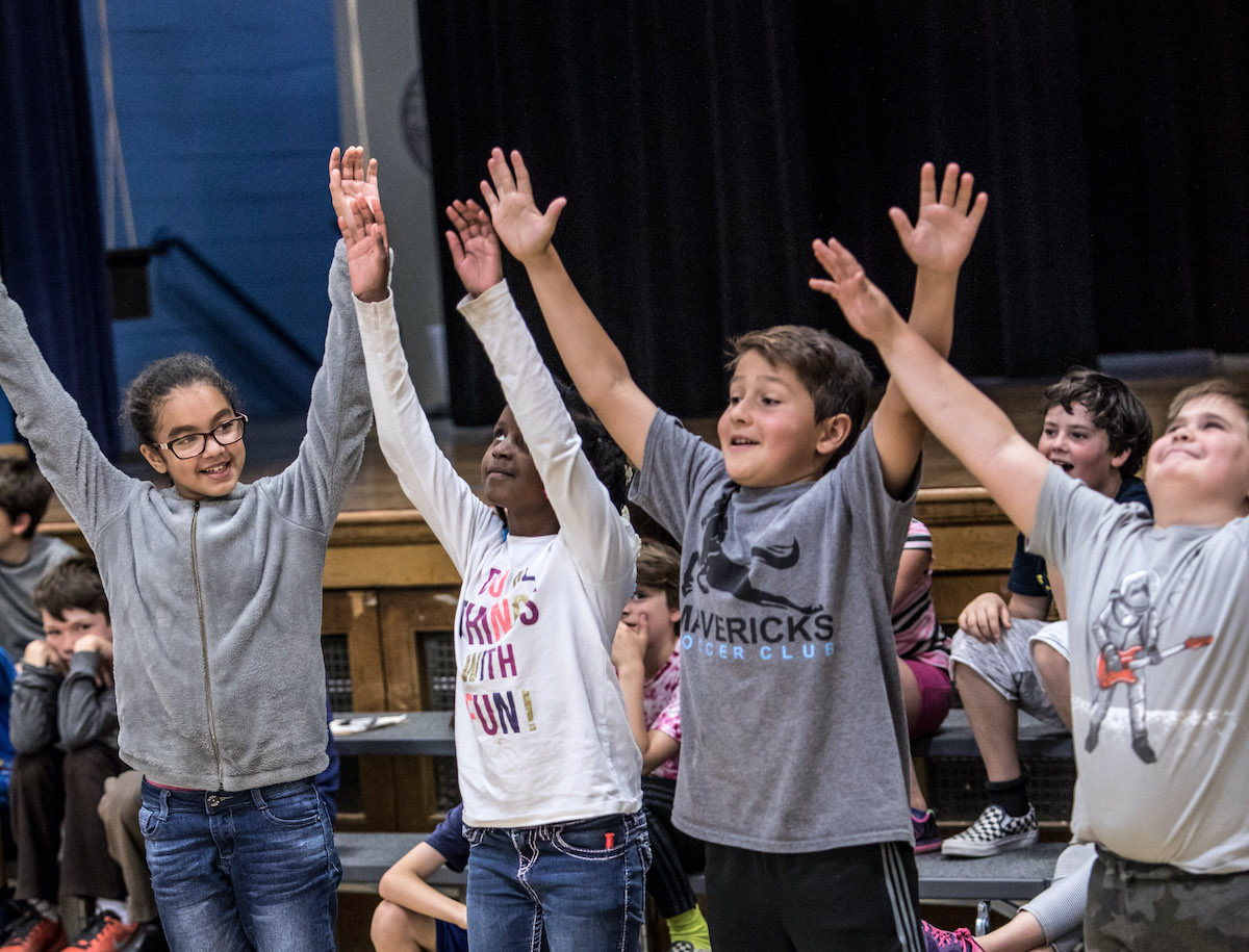 A group of young students with their arms raised at an in-school dance class.
