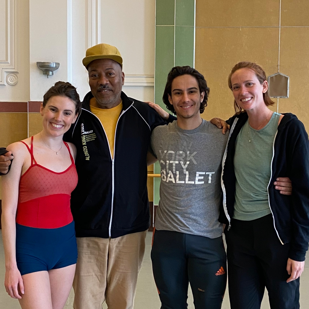 Left to Right: Tiler Peck, Alonzo King, Roman Mejia, Maddie DeVries, standing and smiling together in Studio 5 at LINES Dance Center
