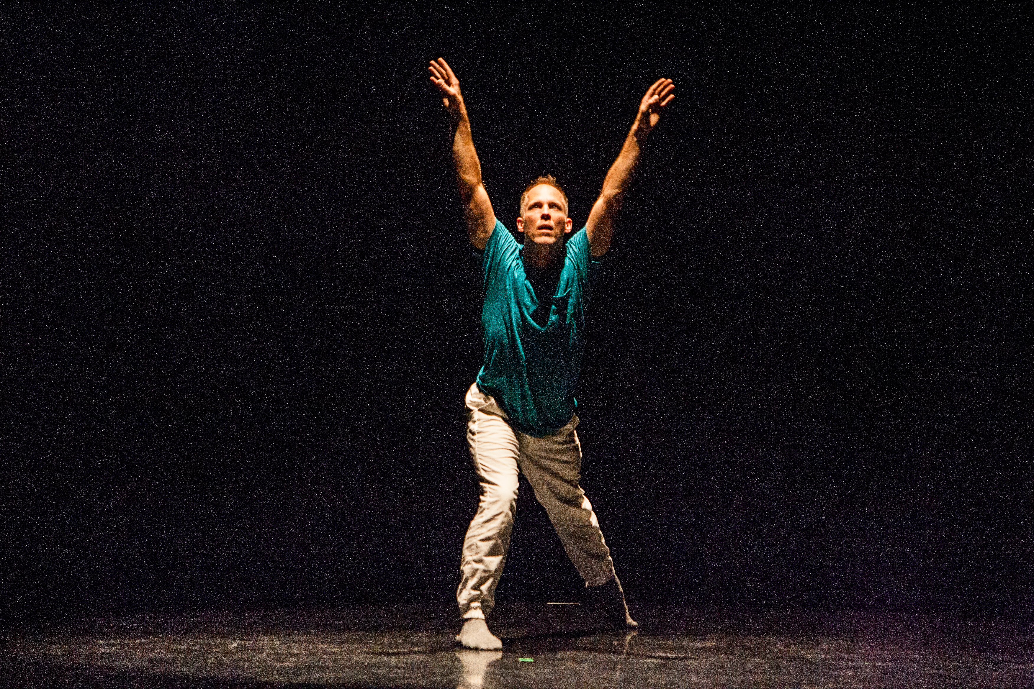Christian Burns on stage at the Ziru SV Festival, looking up with arms extended up in a V-shape