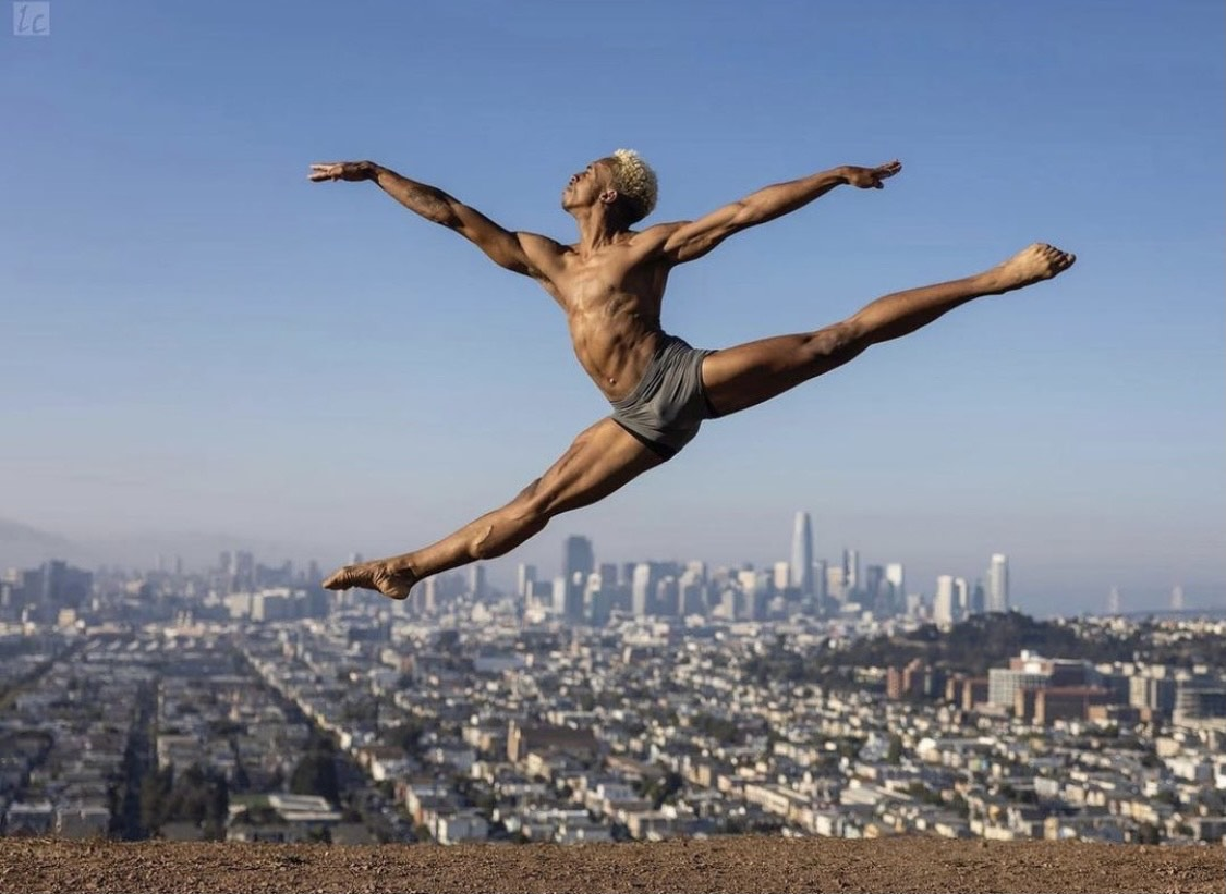 Brandon Graham in split jump, pointed feet, city landscape and blue sky in the background