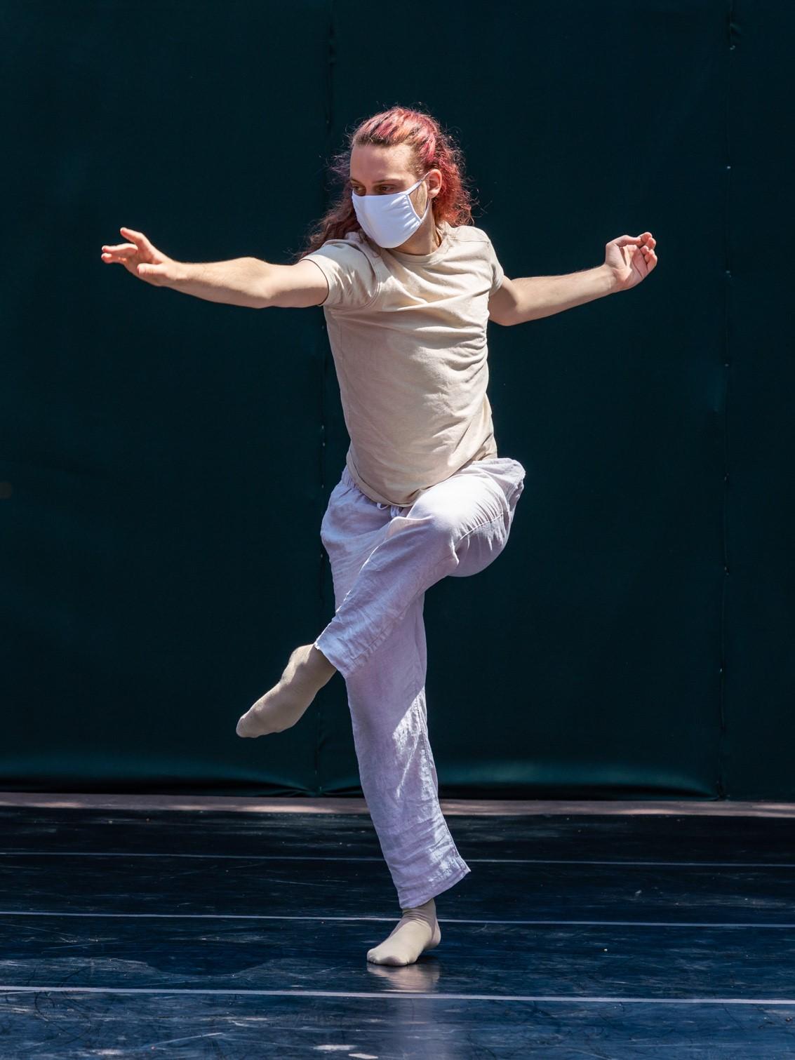 BFA Senior Drake Simon performing outdoors in a mask, leg in front attitude, arm extended forward