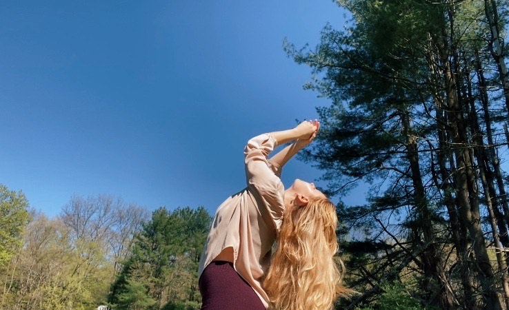 BFA Senior Madeleine Friedman, chest lifted to the blue sky, hands held together over head, green trees in the background