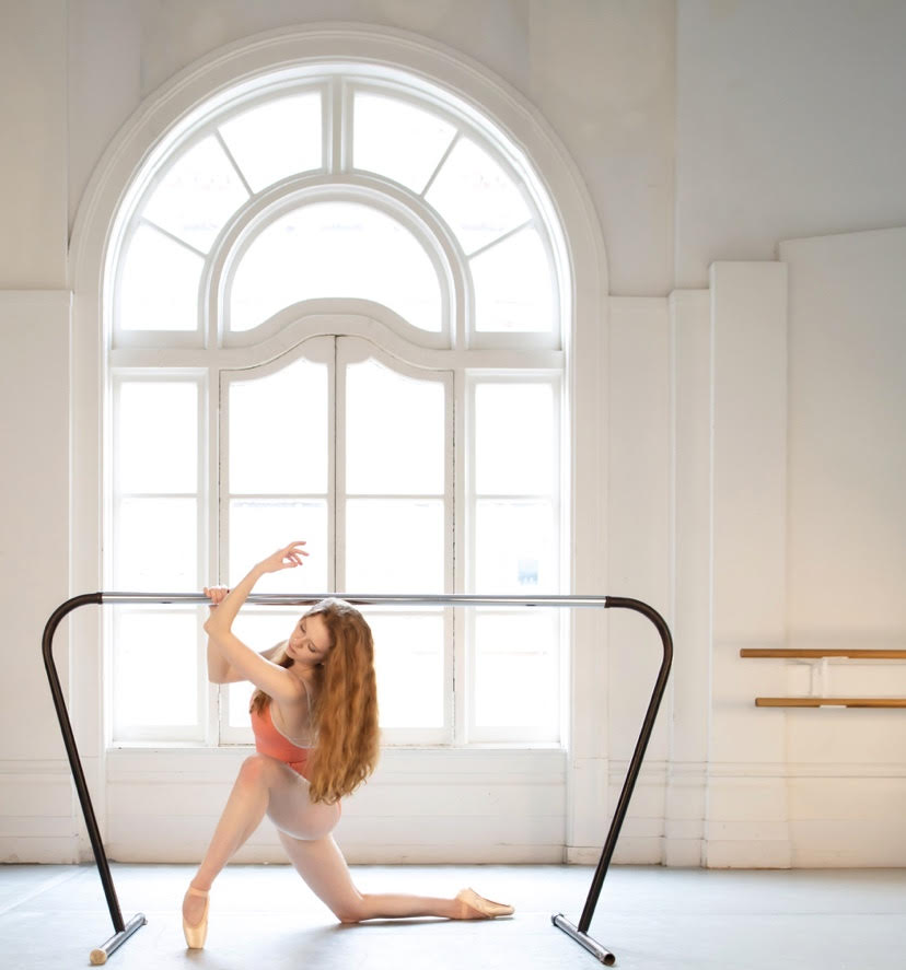 BFA Senior Rowan Williams in a lunge in pointe shoes, holding onto a ballet barre at LINES Dance Center in front of a window